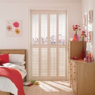 Bedroom with white wooden shutters
