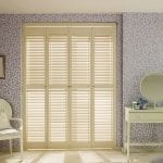 Cream coloured shutters in a bedroom